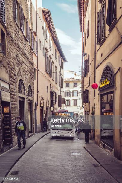 Florence street and historic buildings. Bus moving forward on the narrow street