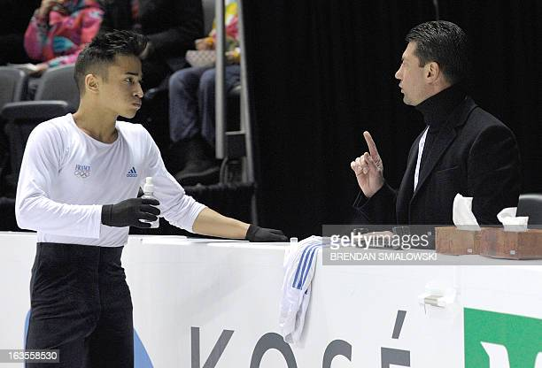 Florent Amodio competing for France speaks with his coach Nikolai Morozov while practicing at Budweiser Gardens in preparation for the 2013 World...