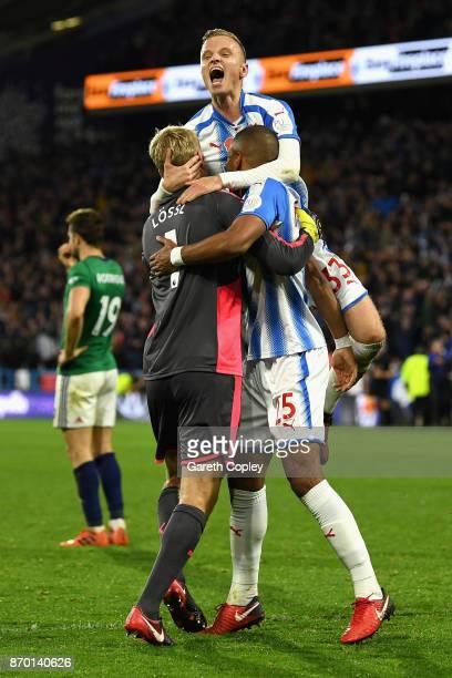 Florent Hadergjonaj of Huddersfield Town celebrates with Jonas Lossl of Huddersfield Town and Mathias Jorgensen of Huddersfield Town during the...