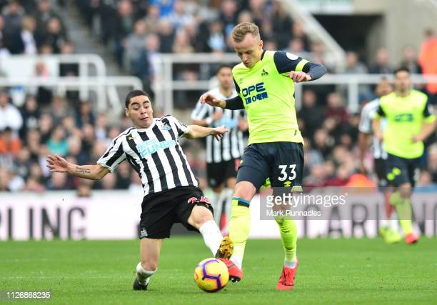 Florent Hadergjonaj of Huddersfield Town challenges for the ball with Miguel Almiron of Newcastle UniCiaran Clark of Newcastle United during the...