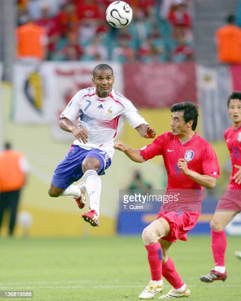 Florent Malouda of France beats Jin Cheul Choi of Korea Republic to a high ball during the Group G match at the Centralstadium in Leipzig Germany on...