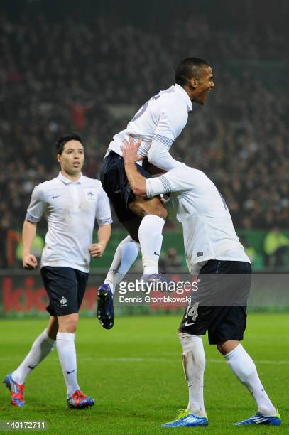 Florent Malouda of France celebrates with teammates Samir Nasri and Jeremy Menez after scoring his team's second goal during the International...