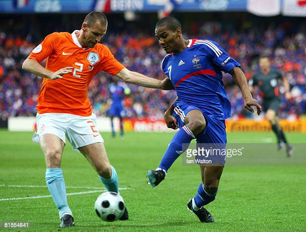 Florent Malouda of France is challenged by Andre Ooijer of Netherlands during the UEFA EURO 2008 Group C match between Netherlands and France at...