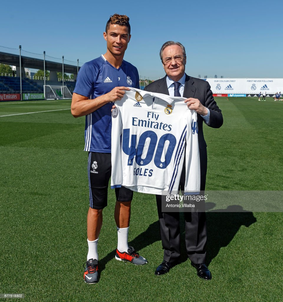 Florentino Perez President of Real Madrid (R) hands a shirt to Cristiano Ronaldo to mark him reaching 400 goals at Valdebebas training ground on May 3, 2017 in Madrid, Spain.