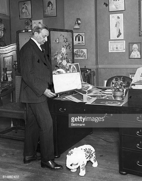 Florenz Ziegfeld American theatrical producer in his office looking at photos of aspiring showgirls