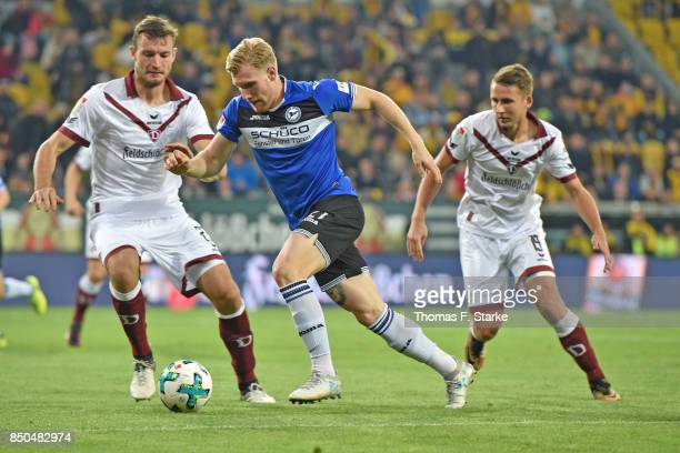 Florian Ballas and Paul Seguin of Dresden tackle Andreas Voglsammer of Bielefeld during the Second Bundesliga match between SG Dynamo Dresden and DSC...