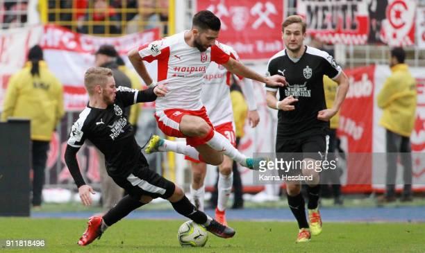 Florian Bruegmann of Jena challenges Hilal ElHelwe of Halle during the 3Liga match between FC Carl Zeiss Jena and Hallescher FC at Ernst Abbe...