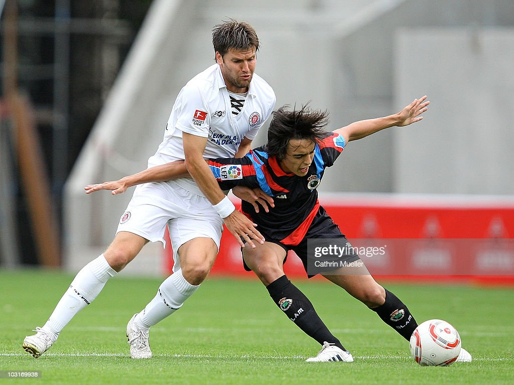 Florian Bruns of St. Pauli battles for the ball with Edu Bedia of Santander during the pre-season friendly match between FC St. Pauli and Racing Santander at Millerntor Stadium on July 30, 2010 in Hamburg, Germany.
