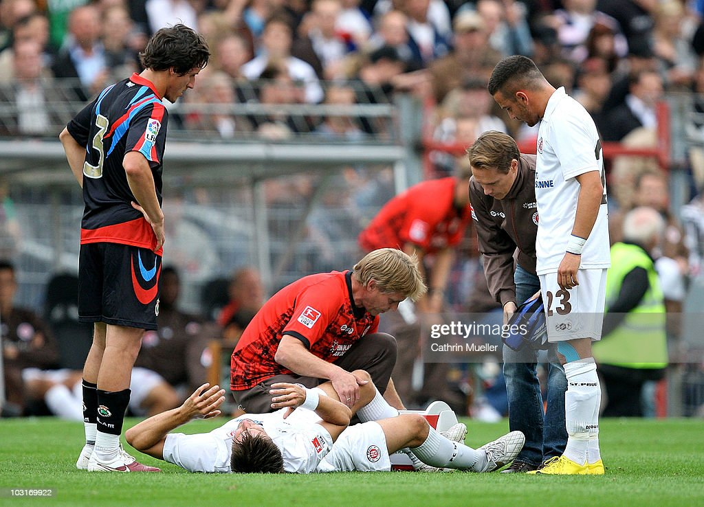Florian Bruns (C) of St. Pauli lies injured on the ground during the pre-season friendly match between FC St. Pauli and Racing Santander at Millerntor Stadium on July 30, 2010 in Hamburg, Germany.