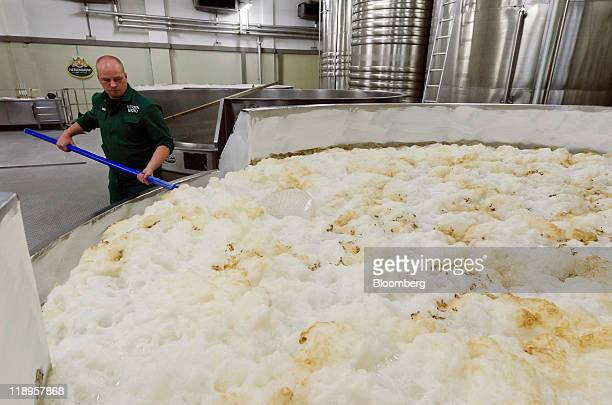 Florian Buchstaller a brewer skims wheat beer in a fermentation tank at Herrnbraeu Gmbh Co KG's brewery in Ingolstadt Germany on Tuesday July 12 2011...
