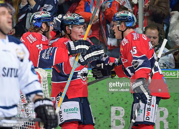 Florian Busch, Antti Miettinen and T.J. Mulock of the Eisbaeren Berlin celebrate after scoring the 1:2 during the game between Eisbaeren Berlin and...