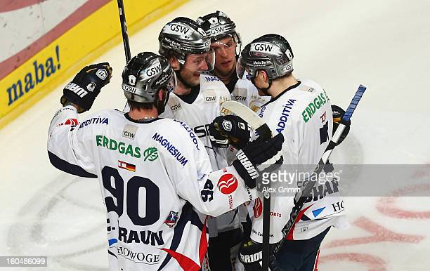 Florian Busch of Berlin celebrates his team's fourth goal with team mates during the DEL match between Adler Mannheim and Eisbaeren Berlin at SAP...