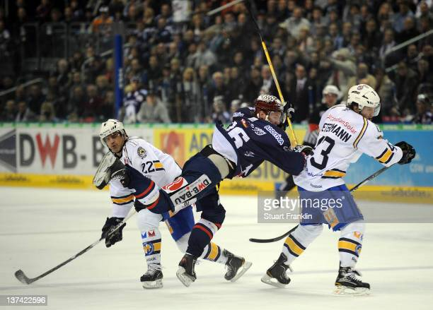 Florian Busch of Berlin is challenged by Julien Stephane and Felix Petermann of Muenchen during the DEL match between Eisbaeren Berlin and EHC...