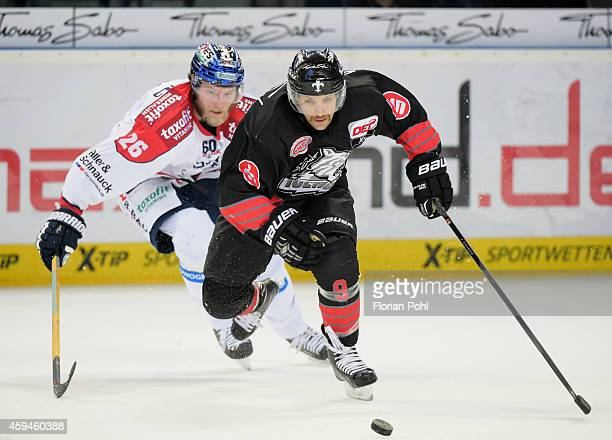 Florian Busch of the Eisbaeren Berlin and Evan Kaufmann of the Thomas Sabo Ice Tigers Nuernberg duel during the game between Thomas Sabo Ice Tigers...