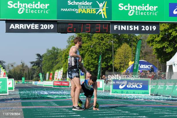 Florian Carvalho helps Benjamin Malaty who felt after the finish line during the Marathon of Paris on April 14 2019 in Paris France