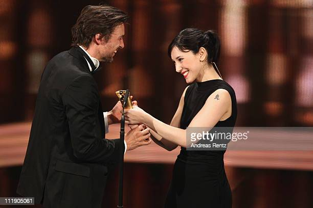 Florian David Fitz receives the Lola for Best Actor from Sibel Kekilli during the German Film Award 2011 at Friedrichstadtpalast on April 8 2011 in...