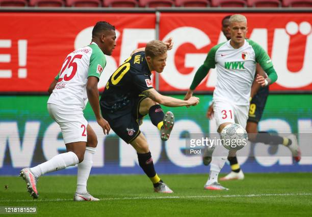 Florian Kainz of 1. FC Koeln is challenged by Carlos Gruezoduring of FC Augsburg the Bundesliga match between FC Augsburg and 1. FC Koeln at...