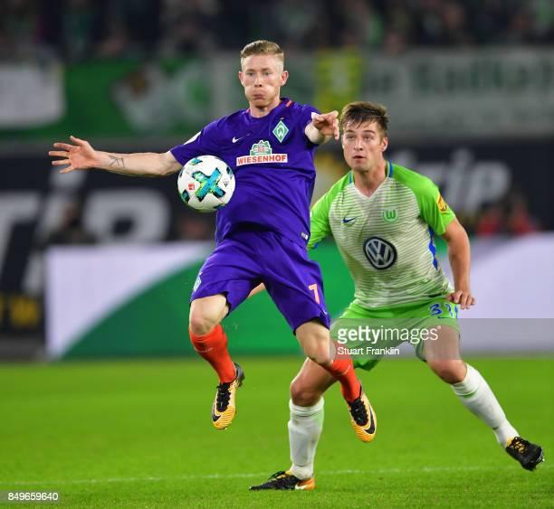 Florian Kainz of Bremen is challenged by Robin Knochen of Wolfsburg during the Bundesliga match between VfL Wolfsburg and SV Werder Bremen at...