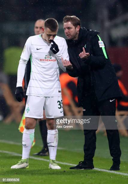 Florian Kohfeldt head coach of Bremen talks to Maximilian Eggestein during the DFB Cup quarter final match between Bayer Leverkusen and Werder Bremen...