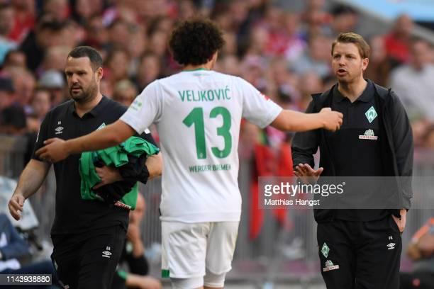 Florian Kohfeldt, Manager of Werder Bremen talks to Milos Veljkovic of Werder Bremen as he leaves the pitch after being sent off during the...