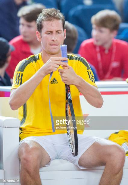 Florian Mayer from Germany works on his racket during his match against Schwartzman from Argentina in the men's singles at the Tennis ATPTour German...
