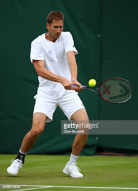 Florian Mayer of Germany plays a backhand during the Men's Singles first round match against Dominic Thiem of Austria on day three of the Wimbledon...