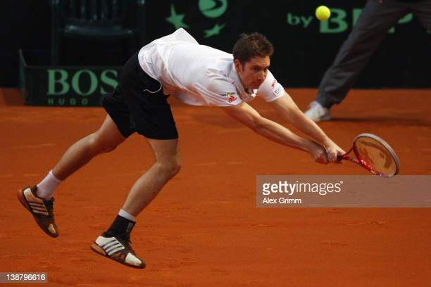 Florian Mayer of Germany returns the ball to Juan Ignacio Chela of Argentina on day 3 of the Davis Cup World Group first round match between Germany...
