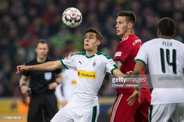 Florian Neuhaus of Borussia Moenchengladbach and Niklas Suele of FC Bayern Muenchen battle for the ball during the Bundesliga match between Borussia...