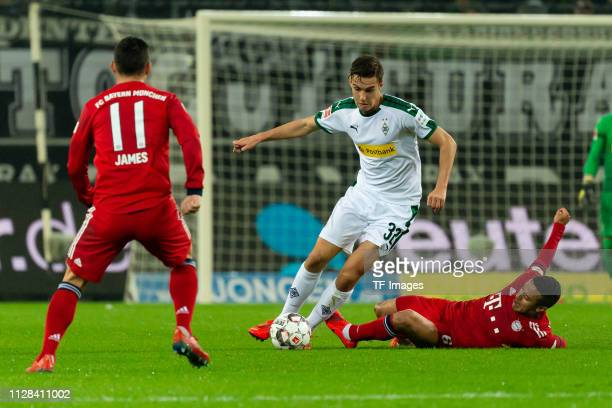Florian Neuhaus of Borussia Moenchengladbach and Thiago of Bayern Muenchen battle for the ball during the Bundesliga match between Borussia...