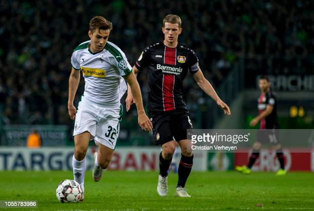 Florian Neuhaus of Borussia Moenchengladbach is chased by Lars Bender of Bayer 04 Leverkusen during the DFB Cup match between Borussia...