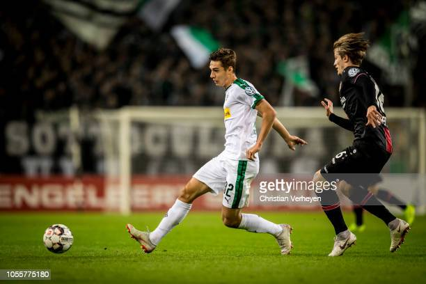 Florian Neuhaus of Borussia Moenchengladbach is chased by Tin Jedvaj of Bayer 04 Leverkusen during the DFB Cup match between Borussia...