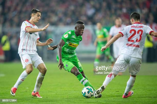 Florian Neuhaus of Duesseldorf, Denis Zakaria of Moenchengladbach and Niko Giesselmann of Duesseldorf fight for the ball during the DFB Cup match...