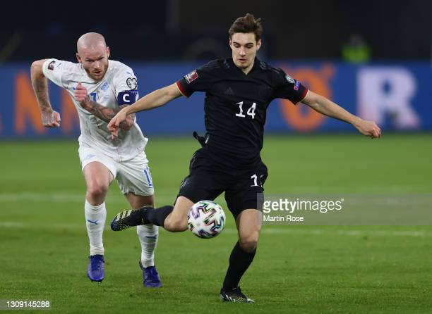 Florian Neuhaus of Germany is put under pressure by Aron Gunnarsson of Iceland during the FIFA World Cup 2022 Qatar qualifying match between Germany...
