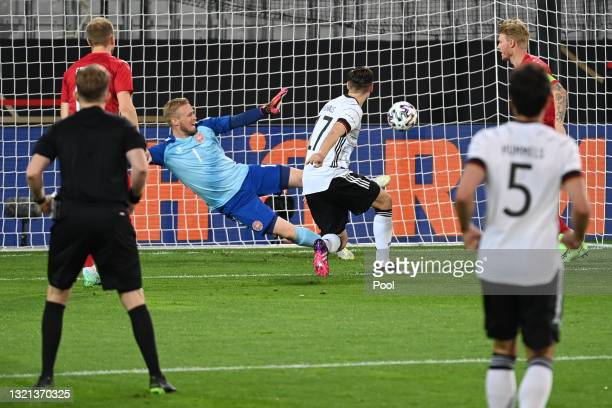 Florian Neuhaus of Germany scores their side's first goal past Kasper Schmeichel of Denmark during the international friendly match between Germany...