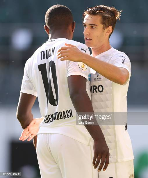 Florian Neuhaus of Moenchengladbach celebrates his team's eighth goal with teammates Marcus Thuram during the DFB Cup first round match between FC...