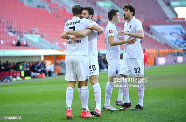 Florian Niederlechner of Augsburg celebrates with teammate Daniel Caligiuri and Tobias Strobl after scoring their team's first goal during the...