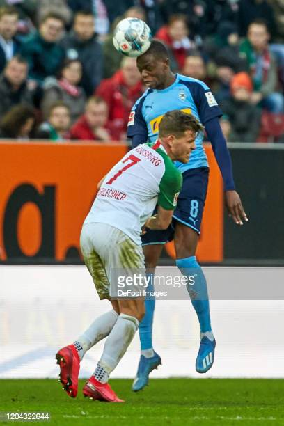 Florian Niederlechner of FC Augsburg and Denis Zakaria of Borussia Moenchengladbach battle for the ball during the Bundesliga match between FC...