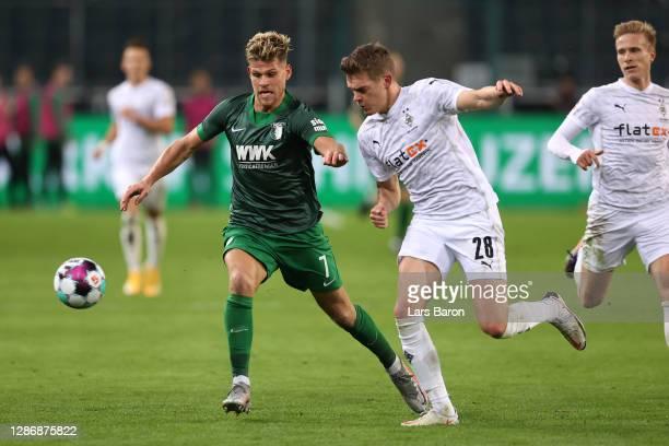 Florian Niederlechner of FC Augsburg battles for possession with Matthias Ginter of Borussia Monchengladbach during the Bundesliga match between...