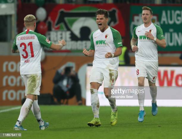 Florian Niederlechner of FC Augsburg celebrates his goal with teammates Philipp Max and Andre Hahn during the Bundesliga match between FC Augsburg...