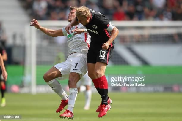 Florian Niederlechner of FC Augsburg crashes head to head with Martin Hinteregger of Eintracht Frankfurt during the Bundesliga match between...