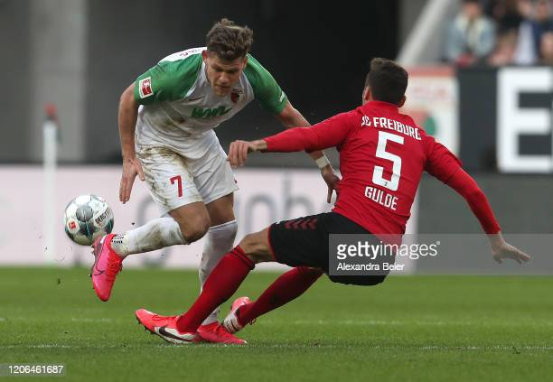 Florian Niederlechner of FC Augsburg fights for the ball with Manuel Gulde of SC Freiburg during the Bundesliga match between FC Augsburg and...
