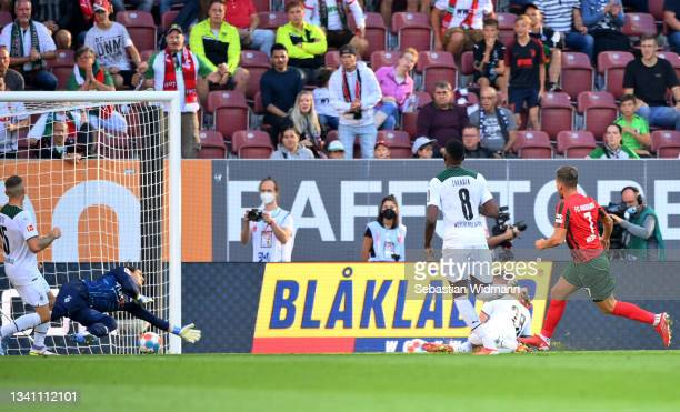 Florian Niederlechner of FC Augsburg scores their side's first goal during the Bundesliga match between FC Augsburg and Borussia Mönchengladbach at...