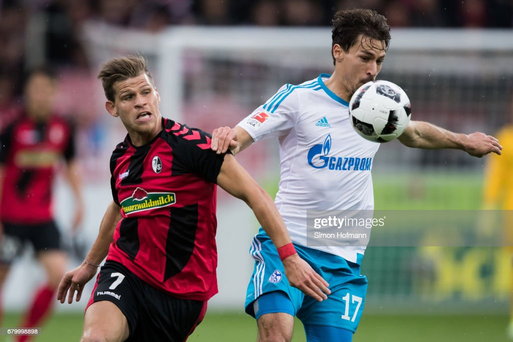 Florian Niederlechner of Freiburg is challenged by Benjamin Stambouli of Schalke during the Bundesliga match between SC Freiburg and FC Schalke 04 at Schwarzwald-Stadion on May 7, 2017 in Freiburg im Breisgau, Germany.