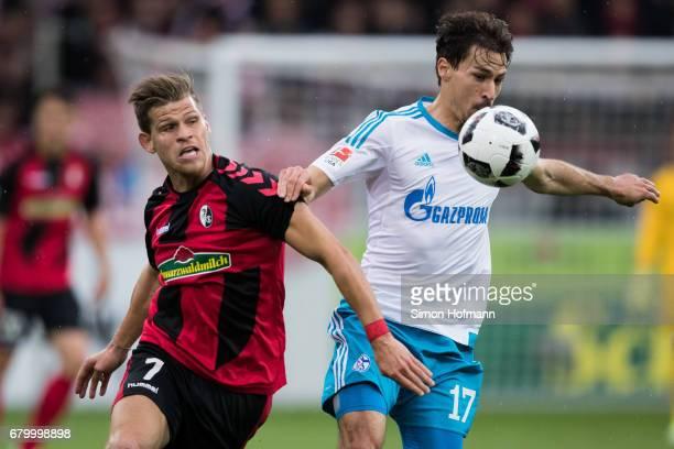 Florian Niederlechner of Freiburg is challenged by Benjamin Stambouli of Schalke during the Bundesliga match between SC Freiburg and FC Schalke 04 at...