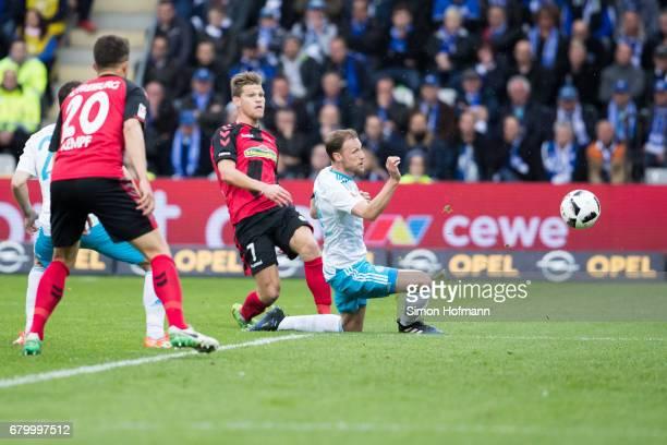 Florian Niederlechner of Freiburg scores his team's first goal against Benedikt Hoewedes of Schalke during the Bundesliga match between SC Freiburg...