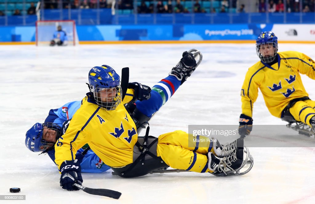 Florian Planker (L) of Italy battles for the puck with Peter Nilsson of Sweden in the Ice Hockey Preliminary Round - Group A game between Italy and Sweden during day three of the PyeongChang 2018 Paralympic Games on March 12, 2018 in Gangneung, South Korea.