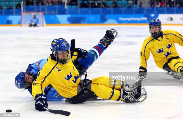 Florian Planker of Italy battles for the puck with Peter Nilsson of Sweden in the Ice Hockey Preliminary Round Group A game between Italy and Sweden...