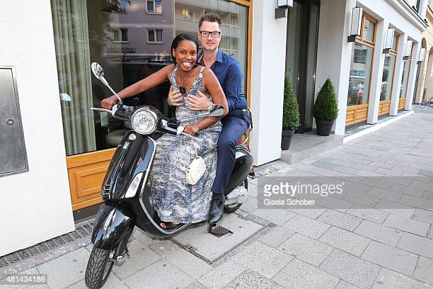 Florian Simbeck and his wife Stephanie Simbeck on a motor roller during the opening of the Grey's Bar at H'Otello on July 20 2015 in Munich Germany