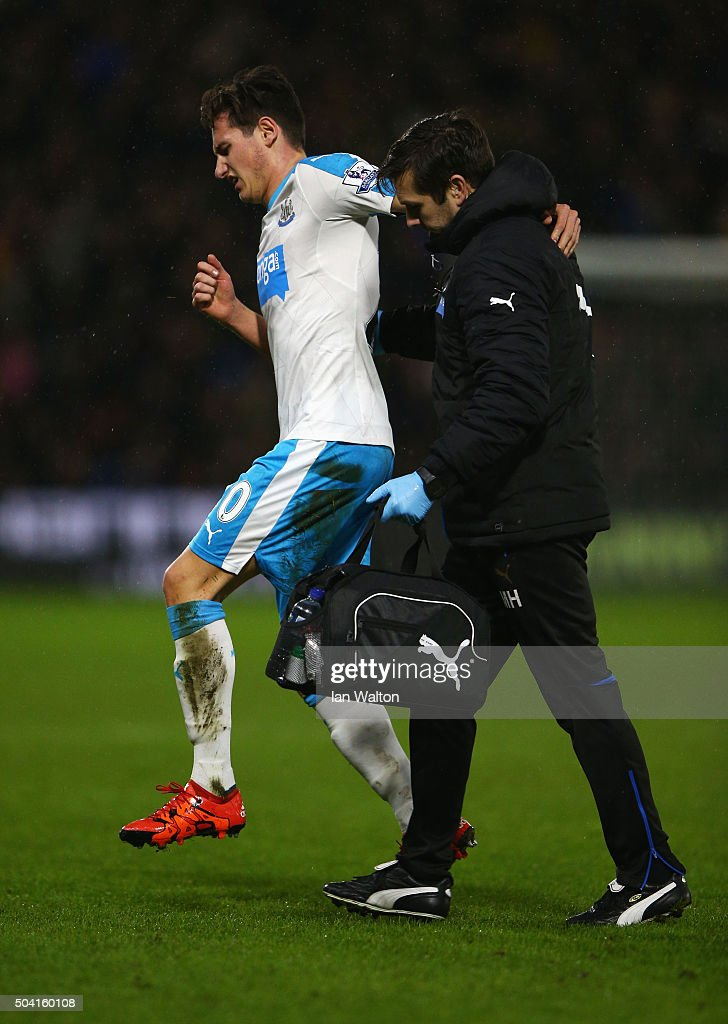 Florian Thauvin of Newcastle United hops off the pitch helped by a medical staff during the Emirates FA Cup Third Round match between Watford and Newcastle United at Vicarage Road on January 9, 2016 in Watford, England.