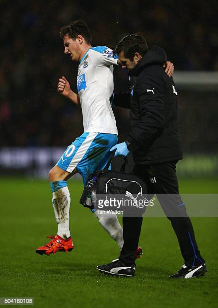 Florian Thauvin of Newcastle United hops off the pitch helped by a medical staff during the Emirates FA Cup Third Round match between Watford and...